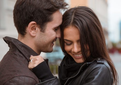Portrait of a smiling young couple hugging outdoors
